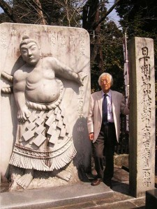 明石志賀之助石像の横に立つ中村弘さん。陣幕が建立し、戦後移設された石碑もある=宇都宮市塙田の蒲生神社